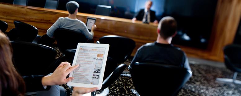 Personen mit iPad bei einer Podiumsdiskussion